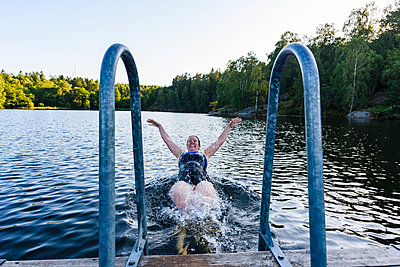 Happy woman swimming in lake - p312m1522266 by Mikael Svensson