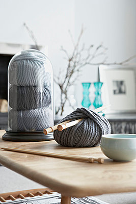 Ball of grey wool with knitting needles on coffee table in London home UK - p349m695311 by Jon Day