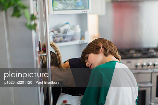 Mother and son looking into refrigerator - p1023m2201120 by Paul Bradbury