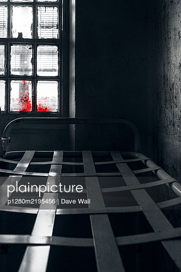 Steel bed frame in prison cell with blood on the window - p1280m2195456 by Dave Wall