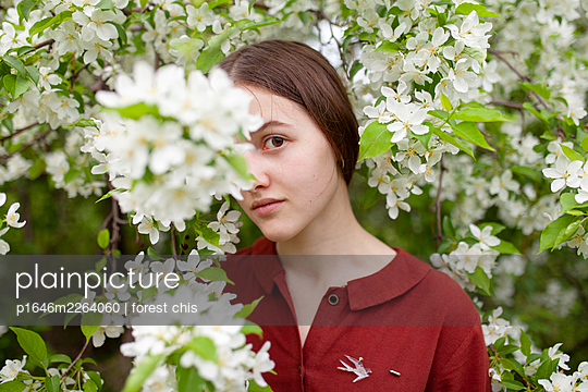 Young woman between blooming bush, portrait - p1646m2264060 by Slava Chistyakov