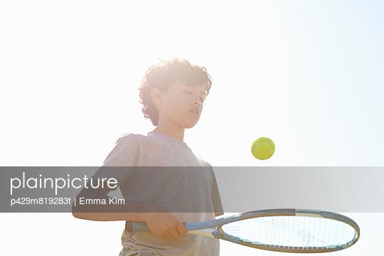 Boy bouncing ball on tennis racket