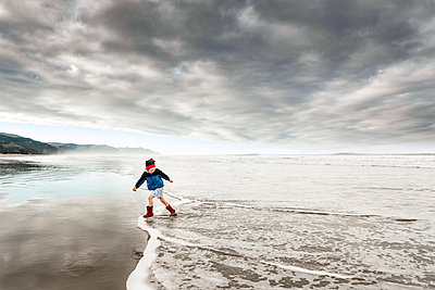 Child running in water at New Zealand beach on cloudy afternoon - p1166m2171917 by Cavan Images