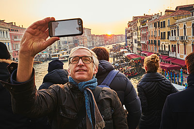 Man takes a selfie on Rialto Bridge in the evening sun - p1312m2082163 by Axel Killian