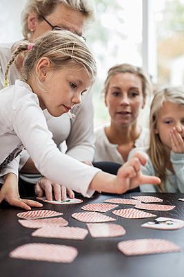 Girl playing card puzzle game with family at home - p426m896693f by Maskot
