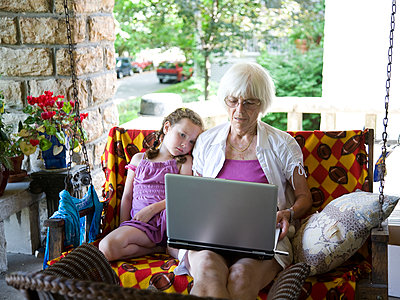 Grandmother and granddaughter using laptop on porch - p555m1408643 by Shestock