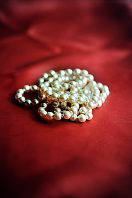 Pearl necklace on red fabric, close-up - p1072m2158725 by Neville Mountford-Hoare