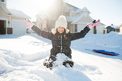 Girl 10-12 years old having fun in the snow in front of house - p1166m2136754 by Cavan Images