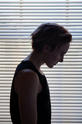Woman silhouette in front of blinds  - p1248m2047714 by miguel sobreira