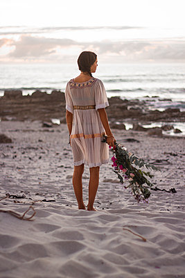 Teenage girl with bunch of flowers on the beach - p1640m2246203 by Holly & John