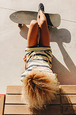 Blond Afro woman reclining with skateboard on sunny day - p300m2221588 by Manu Reyes