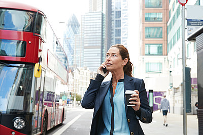Businesswoman with coffee cup talking on mobile phone while standing in city - p300m2227046 by Pete Muller