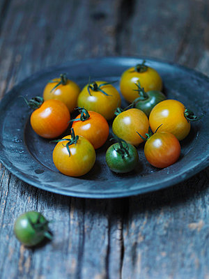 Plate of yellow cherry tomatoes - p429m757549f by Danielle Wood