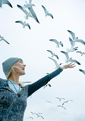Woman holding arm up to sky where seagulls are flying - p6238107f by Laurence Mouton