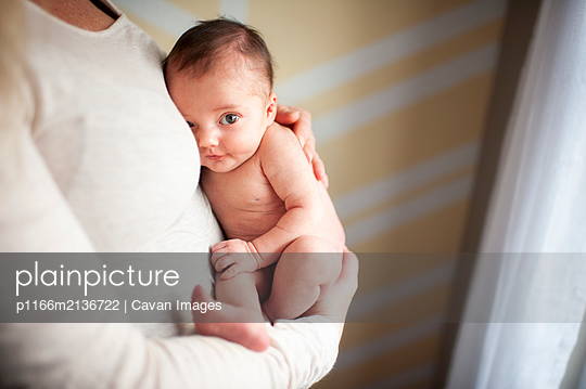 Mother holding looking newborn baby girl against chest at home - p1166m2136722 by Cavan Images