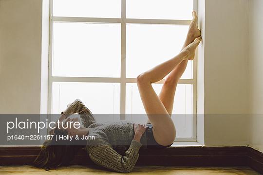Junge Frau liegt entspannt auf einer Fensterbank - p1640m2261157 von Holly & John
