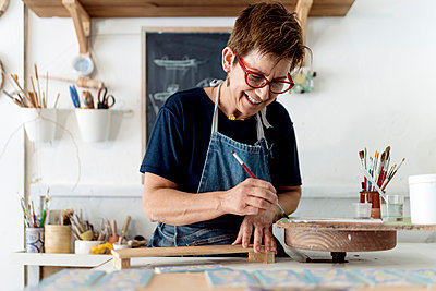 Smiling owner painting craft product in ceramic workshop - p300m2240345 by Ezequiel Giménez