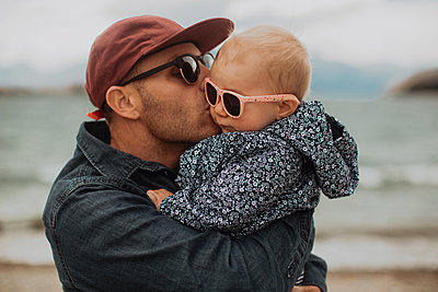 Father kissing baby on beach - p924m2098231 by Peter Amend