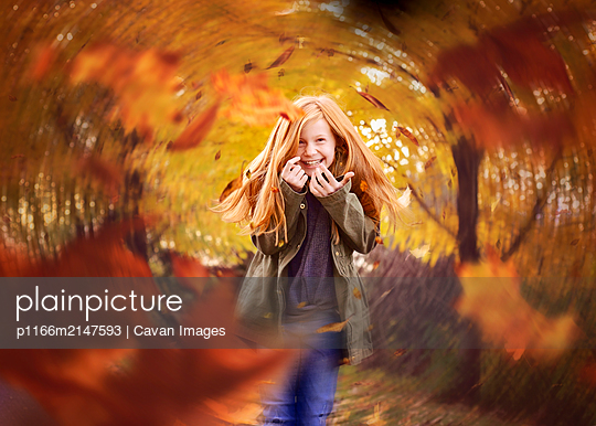 Beautiful Red Haired Girl in Swirling Fall Leaves - p1166m2147593 by Cavan Images