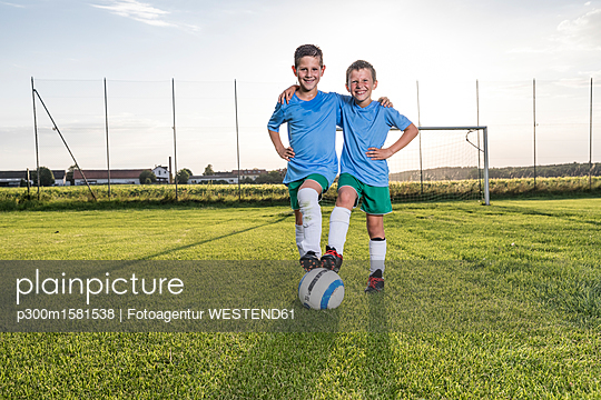 Smiling young football players embracing on football ground - p300m1581538 by Fotoagentur WESTEND61