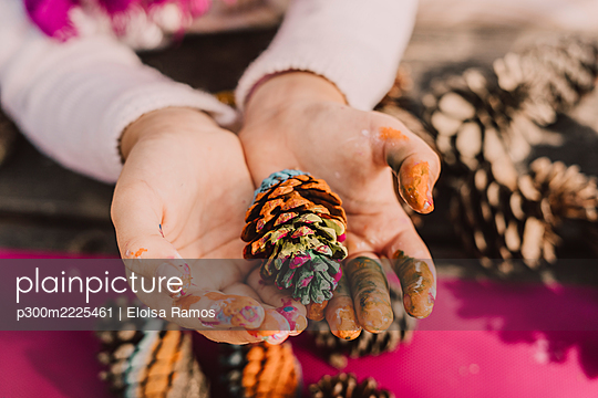 Messy hands of girl with colorful pine cone at picnic table in park - p300m2225461 by Eloisa Ramos