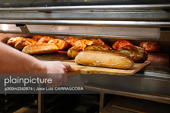 Male chef removing baked breads with pizza peel from oven in bakery - p300m2242874 by Jose Luis CARRASCOSA