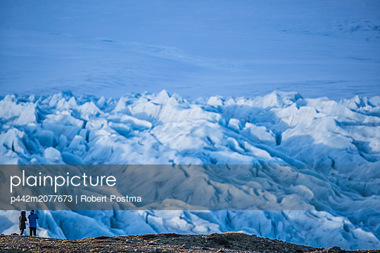 Two people hiking and taking photos of a glacier along the South shore of Iceland; Iceland - p442m2077673 by Robert Postma