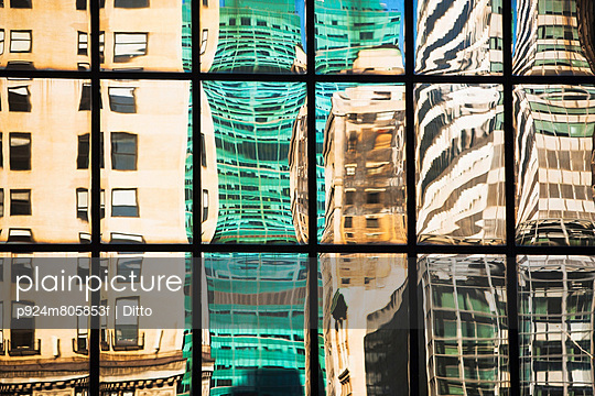 Modern glass facade reflecting varied office buildings