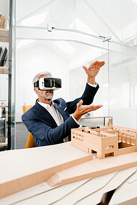 Mature businessman with architectural model in office wearing VR glasses - p300m1494810 by Kniel Synnatzschke