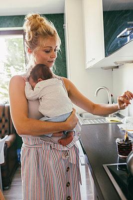 Mother holding newborn baby in kitchen while making tea - p300m2042737 von Mareen Fischinger