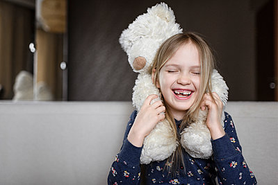 Portrait of laughing little girl with tooth gap holding white teddy bear - p300m2103143 by Ekaterina Yakunina