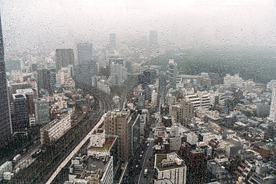 Japan, Tokyo, Downtown buildings on rainy day seen from window - p300m2206664 by klublu