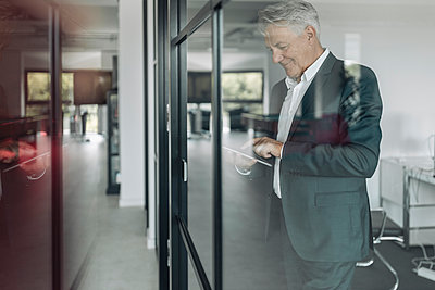 Smiling businessman using digital tablet while standing by glass wall at office - p300m2225766 by Gustafsson