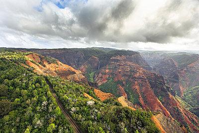 A road leads past Waimea Canyon and Waipoo Falls on the Hawaiian island of Kauai. - p343m1217987 by Matt Andrew