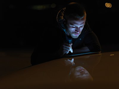 Young man using digital tablet, outdoors, at night, face illuminated - p429m1052763 by Elke Meitzel