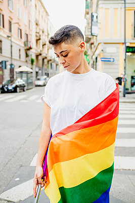 Young lesbian woman standing on a street, wrapped in rainbow flag. - p429m2208588 by Eugenio Marongiu