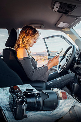 Young woman sitting in vehicle, looking at digital tablet, SLR camera on passenger seat, Mexican Hat, Utah, USA - p924m1580622 by Seth K. Hughes