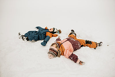Canada, Ontario, Brother (12-17 months) and sister (2-3) doing snow angels - p924m2271211 by Sara Monika