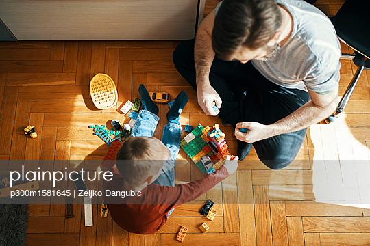 Father and son sitting on the floor playing together with building bricks, top view - p300m1581645 von Zeljko Dangubic