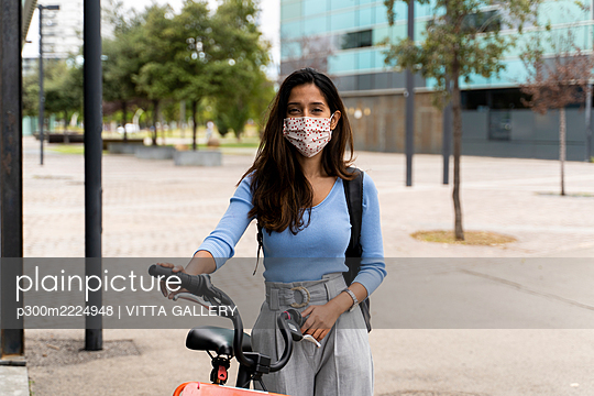Beautiful woman wearing protective face mask while standing with bicycle in city during COVID-19 pandemic - p300m2224948 by VITTA GALLERY