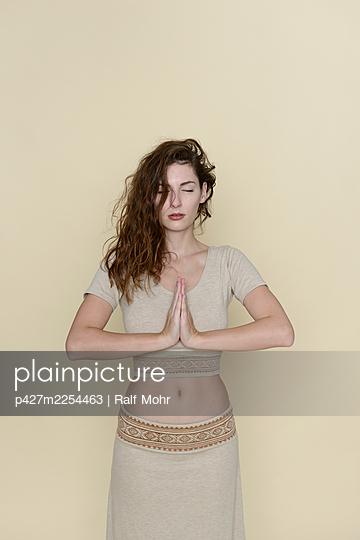 Woman meditating, portrait - p427m2254463 by Ralf Mohr