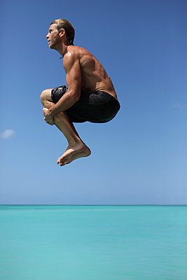 Man jumping into water - p045m899709 by Jasmin Sander