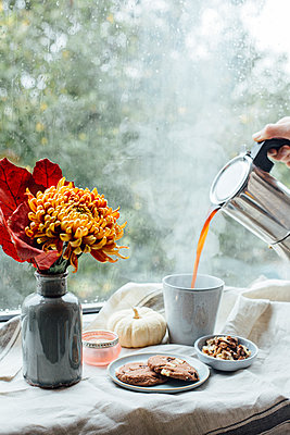 Woman's hand pouring hot coffee into a mug on rainy day - p300m2080478 by Jean Schwarz