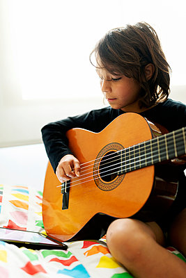 Boy sitting on bed using digital tablet for playing song on guitar - p300m2181135 by Valentina Barreto
