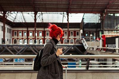 Redheaded woman walking at railroad station - p300m2286635 by Manu Reyes