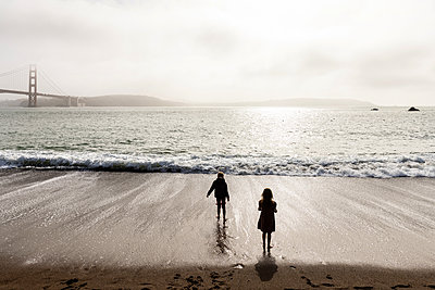 Two children on the beach, Golden Gate Bridge in the background - p756m2295408 by Bénédicte Lassalle
