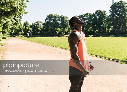 Young athlete exercising on sports field, looking up - p300m2005346 von Uwe Umstätter