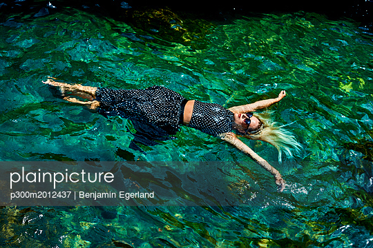 Young woman floating with dress on water in lagoon - p300m2012437 von Benjamin Egerland