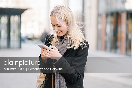 Young woman using cell phone in the city - p300m2102369 by Hernandez and Sorokina