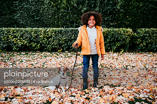 Smiling girl holding pet leash while standing by dog at park - p300m2225833 by Eva Blanco